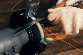 foto of friction  - Knife sharpener and hand with blade on wooden table - JPG