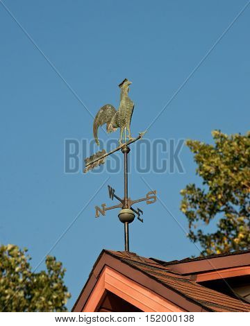 Vintage weather vane cock bird on the red roof above blue sky