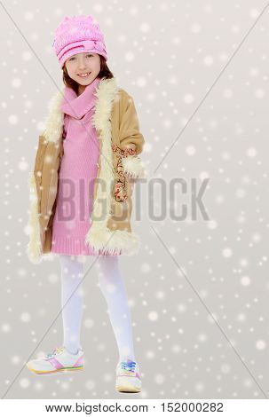 Happy little girl in a pink hat and winter coat with fur. Girl posing in full growth.Gray background with round white snowflakes.
