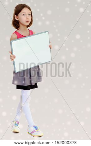 Beautiful, small, slender girl, holding in front of a white poster.Gray background with round white snowflakes.
