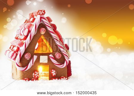 Gingerbread House In Snowy Scenery As Christmas Decoration. Candlelight For Romantic Atmosphere. Golden Background With Bokeh Effect. Copy Space For Advertisement