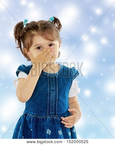 Unhealthy little girl with short pigtails on her head, closed his nose with his hand, the girl sneezes from allergies. Close-up.Blue Christmas festive background with white snowflakes.