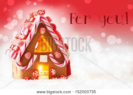 Gingerbread House In Snowy Scenery As Christmas Decoration. Candlelight For Romantic Atmosphere. Red Background With Bokeh Effect. English Text For You