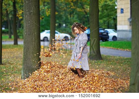 Beautiful smiling girl with dreadlocks in a lavender cloak having fun in the alley between the trees , jumping on a pile of yellow leaves.