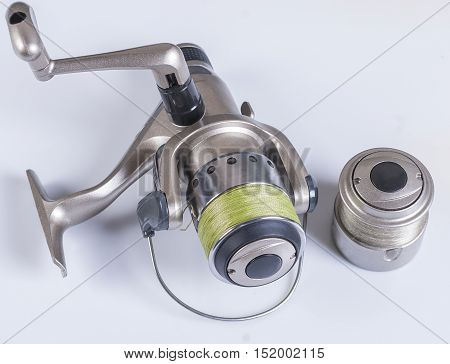 Spinning reel with fishing line wrapped around the green on a white background. not isolated