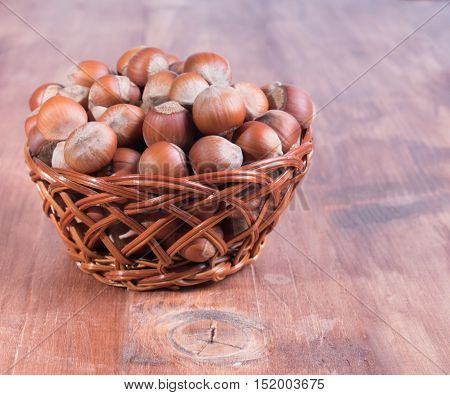 Hazelnuts in a basket on wooden background.