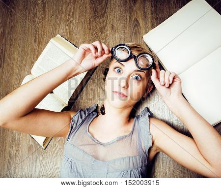 portrait of crazy student girl in glasses with books and cockroaches, concept of modern education people, lifestyle portrait in interior close up