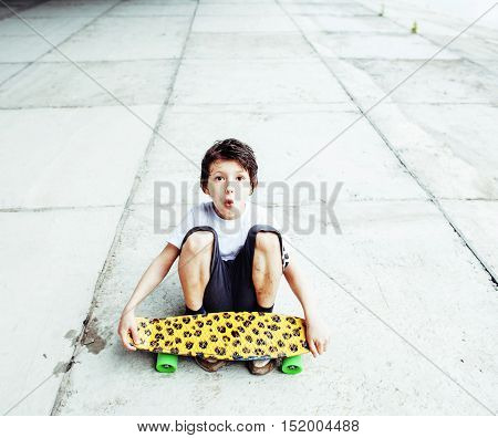 little cute boy with skateboard on playground alone training, making funy faces, lifestyle people concept close up