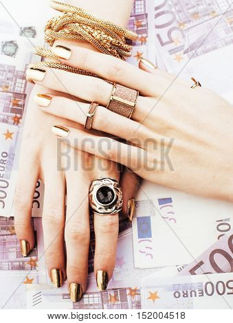 hands of rich woman with golden manicure and many jewelry rings on cash euros close up five hundred, modern money concept