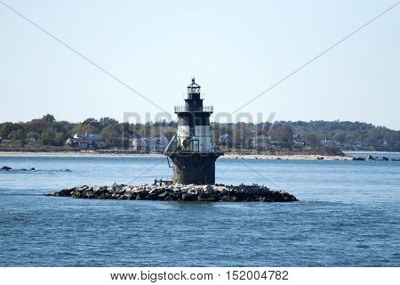 The Orient Point Lighthouse taken from the water. Seaweed is visable on the lightouse and Orient points beach is in the background