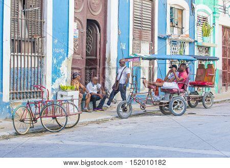 HAVANA CUBA - JULY 18 : A Cuban rickshaw drivers in old Havana street on July 18 2016. Rickshaw are a popular way of transport in Cuba