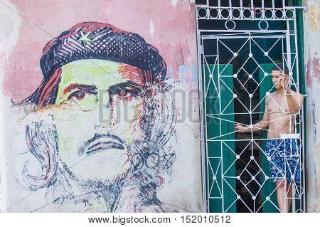HAVANA CUBA - JULY 18 : Cuban man stand near mural of Che Guevara in old Havana street on July 18 2016. The historic center of Havana is UNESCO World Heritage Site since 1982.