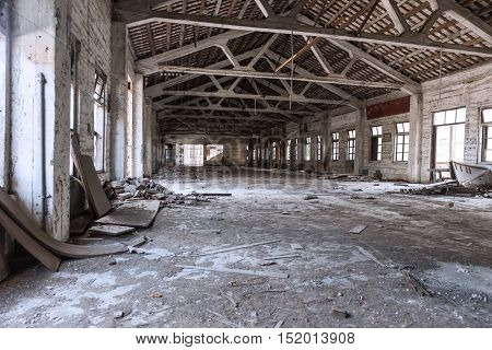 Empty industrial loft in an architectural background with bare cement walls floors and pillars supporting a mezzanine