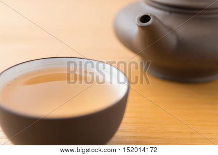 cup of tea and teapot on wood table close up