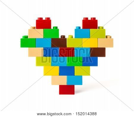 Heart made from colorful toy bricks on white with clipping path