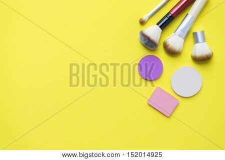 Set of colorful cosmetics on yellow background
