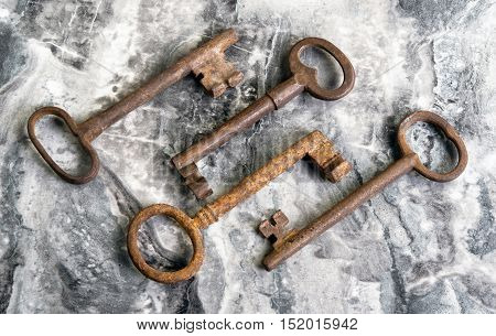 Antique iron skeleton keys on marble table.