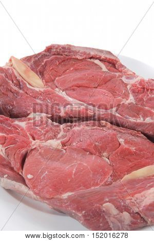 two fresh raw red ribeye beef steak on big white plate isolated over white background rib eye