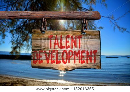 Talent development motivational phrase sign on old wood with blurred background