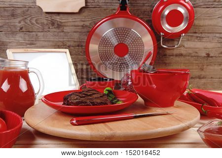 red theme lunch fresh grilled bbq roast beef steak red plate  green chili tomato soup ketchup sauce paprika  glass ground pepper american  modern cutlery served wooden plate  table empty menu board