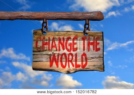 Change the world motivational phrase sign on old wood with blurred background