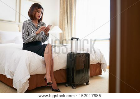 Business lady sitting in hotel room and text messaging