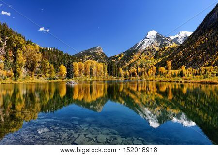 Fall foliage color and big mountain with snow on top. Reflection view of beautiful mountain in Marble county Colorado.