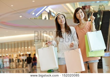 Korean young women making purchases in shopping mall