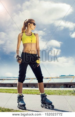 Fit, sporty and athletic young woman. Beautiful girl on skates in a sportswear.