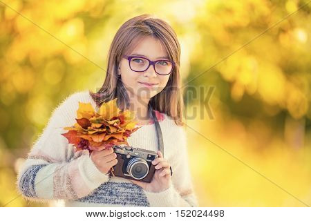 Autumn time. The teenage attractive cute young girl with autumn bouquet and retro camera. Young girl photographer autumn season.