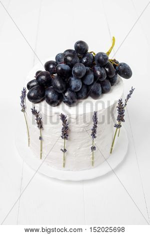 Top view of the homemade sour cream cake decorated with grapes and lavender on a white wooden background. Minimal style