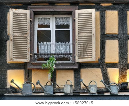 Window on the facade of a half-timbered house with open shutters and watering cans standing on the windowsill.