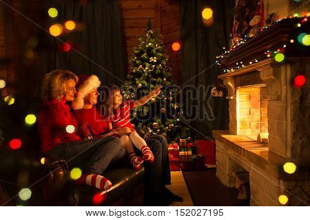 Family near fireplace and Christmas tree in festival decorated house interior