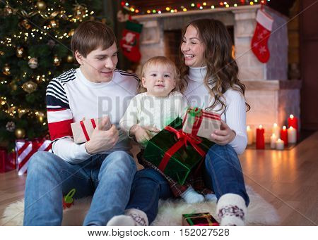 Family exchanging gifts sitting on fur in front of Christmas tree