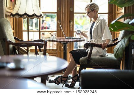 Beautiful blonde girl in glasses sits on armchair at the table in the restaurant and holds a white cup in the right hand. She looks at the laptop. Woman wears black dress and sandals, a white cloak.