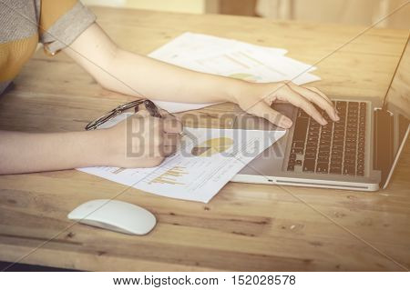 Business girl hand holding pen point stock market chart and using laptop on wood desk. vintage effect.