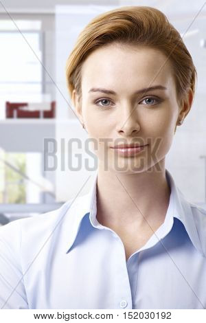 Portrait of young casual attractive caucasian businesswoman, looking at camera.