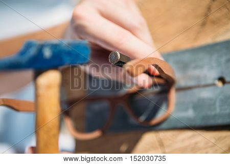 Close up of unrecognizable master crafting wooden spectacles with hammer and chisel on workplace