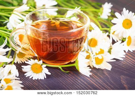 Chamomile tea in a transparent cup on a wooden table. The concept of herbal medicine.