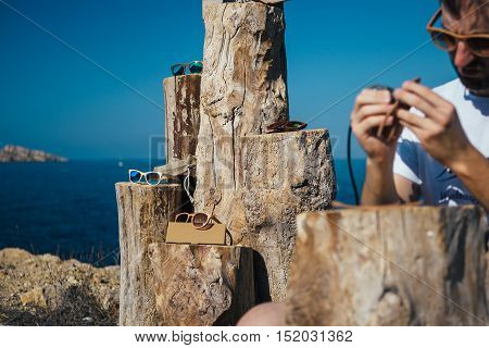 Stylish wooden sunglasses with colorful lenses lying on a wooden pedestal. Craft master on foreground