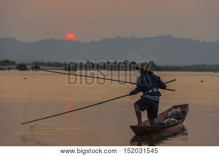 Fishermen fishing in the river at sunset.