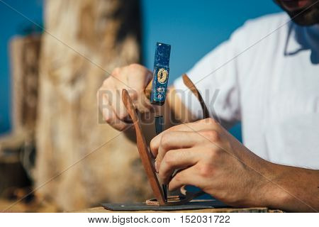 Close up of unrecognizable man crafts wooden sunglasses with hammer and chisel