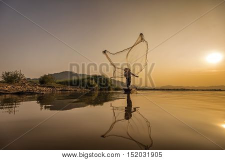 Fishermen fishing at sunset in the river .