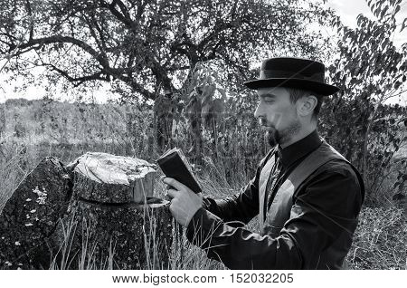Young bearded priest prays in a garden. Black and white photography