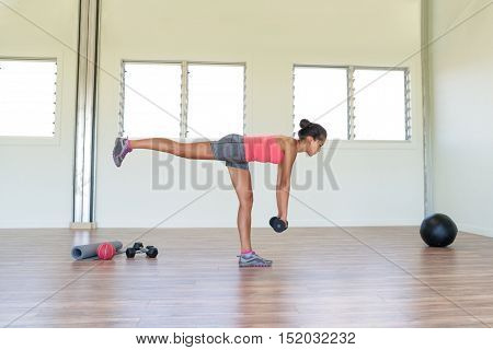 Woman strength training at gym exercising hamstring and lower back muscles with single-leg romanian deadlift exercises with free weights dumbbells. Asian girl alone indoors in fitness center room.