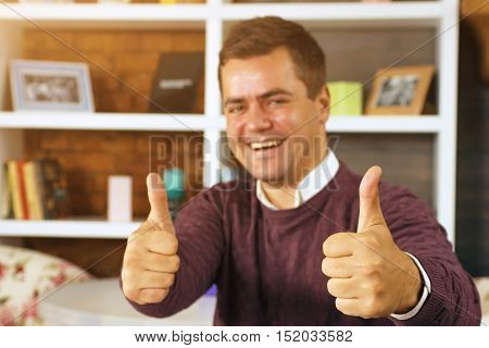 Young man smiling and showing two thumbs up. Home decor background is with shelf and books.
