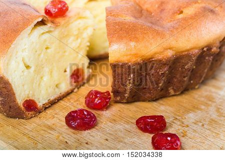 Home-made pie and several red berries nearby. Pie lies on a wooden board from pie the piece is cut off. Close up small depth of sharpness