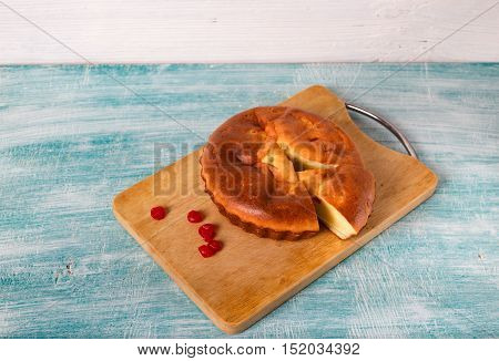 Home-made pie and several red berries nearby. Pie lies on a wooden board a blue table in rural style. From pie the piece is cut off.