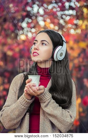 girl in autumn park with takeaway coffee and headphones. Beautiful young woman with music headphones holding a take away coffee cup and listening to the music.