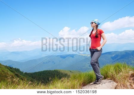 Girl tourist in Carpathian mountains. Hiker posing at the camera in mountains. Lifestyle concept active leisure tourism. Woman traveler on background of mountains and sky copy space. Active young athletic girl